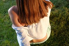 Rear view of redhair teen girl on grass stock images