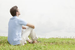 Rear view of relaxed young man sitting on grass against sky Royalty Free Stock Photography