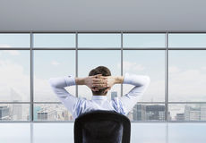 Rear view of the relaxing businessman is in a modern panoramic office. Stock Image