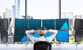 Rear view of a relaxing trader who is sitting in front of a trad Stock Images