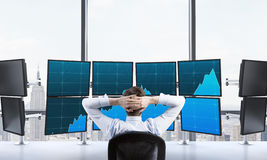 Rear view of a relaxing trader who is sitting in front of a trad Stock Photos