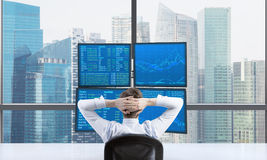 Rear view of a relaxing trader who is sitting in front of a trading station which consists of four screens with financial data. A Stock Images