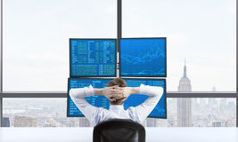 Rear view of a relaxing trader who is sitting in front of a trading station which consists of four screens with financial data. A Royalty Free Stock Photos