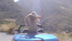 Woman in convertible car. Rear view of relaxing woman with her hands up sitting in blue cabriolet car.Vacation, holiday, journey concept. Slow motion shot of stock video footage