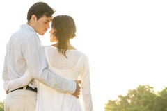 Rear view of romantic couple standing arms around against clear sky Royalty Free Stock Photography