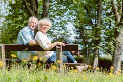 Romantic elderly couple sitting together on a bench in a tranquil day. Rear view of a romantic elderly couple enjoying nature while sitting together on a bench stock photo