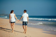 Rear view of romantic happy couple walking on beach holding hands at blue sky and ocean background. Man and woman in stock photo