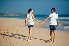 Rear view of romantic happy couple walking on beach holding hands and look at each other at blue sky and ocean royalty free stock photography