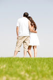 Rear view of romantic young couple standing Stock Images