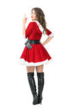 Rear view of rude female Santa Claus flipping middle finger at camera Royalty Free Stock Photo