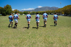 Rear view of rugby team running at field. On sunny day Royalty Free Stock Image
