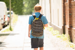 Schoolboy Walking On Sidewalk. Rear View Of A Schoolboy With Backpack Walking On Sidewalk stock photos