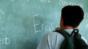 Schoolboy writing english word on chalkboard in classroom stock video