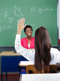 Rear View Of Schoolgirl Raising Hand In Classroom Stock Photo