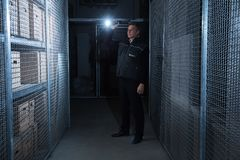 Security Guard Standing In The Warehouse. Rear View Of A Security Guard Standing In The Warehouse Holding Flashlight royalty free stock photo