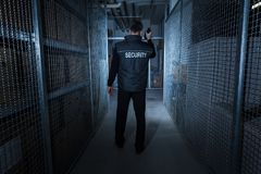 Security Guard Standing In The Warehouse. Rear View Of A Security Guard Standing In The Warehouse Holding Flashlight Stock Images
