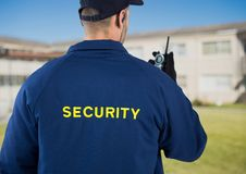 Rear view of security guard using radio against house stock image