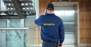 Rear view of security guard waiting for lift while standing in office building. Digital composite of Rear view of security guard waiting for lift while standing stock images