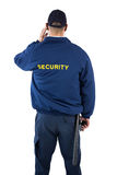 Rear view of security officer listening to earpiece Royalty Free Stock Image
