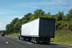 Rear View of Semi Truck on Highway. Semi truck with cargo under blue sky Royalty Free Stock Image