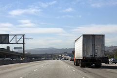Rear View of Semi Truck on Highway. Rear and side view of semi truck on highway under blue sky Stock Images