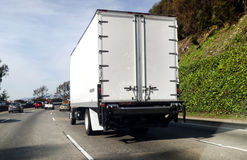 Rear View of Semi Truck on Highway. Rear and side view of white semi truck on highway Royalty Free Stock Image