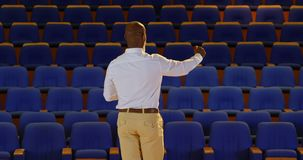African American businessman practicing speech in empty auditorium 4k. Rear view of senior African American businessman practicing speech in empty auditorium. He stock video