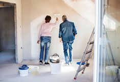 Rear view of senior couple painting walls in new home, relocation concept. stock images