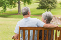 Rear view of senior couple sitting on bench at park Royalty Free Stock Images