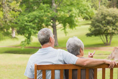 Rear view of senior couple sitting on bench at park Royalty Free Stock Photography