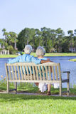 Rear View Senior Couple Sitting On Park Bench. Rear view of a romentic senior couple sitting on a park bench looking at a blue lake stock photo