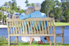 Rear View Senior Couple Sitting On Park Bench. Rear view of a happy romentic senior couple sitting on a park bench embracing looking at a blue lake royalty free stock image