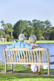 Rear View Senior Couple Sitting On Park Bench. Rear view of a happy romantic senior couple sitting on a park bench looking at a blue lake royalty free stock photography