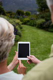 Rear view of senior couple using digital tablet Royalty Free Stock Photo