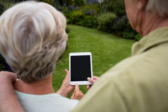 Rear view of senior couple using digital tablet Stock Photo