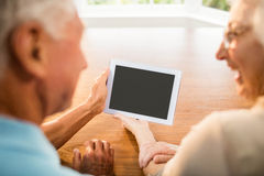 Rear view of senior couple using tablet stock images