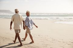 Rear View Of Senior Couple Walking Along Beach Hand In Hand stock image
