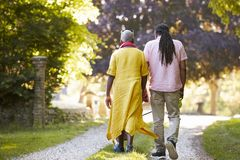Rear View Of Senior Couple Walking Pet Bulldog In Countryside royalty free stock image