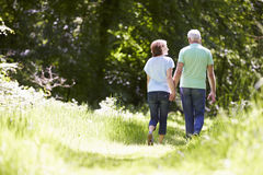 Rear View Of Senior Couple Walking In Summer Countryside Royalty Free Stock Images