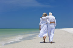 Rear View Senior Couple Walking on Tropical Beach Stock Images