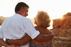 Rear View Of Senior Couple Watching Sunset Over Port Stock Photos