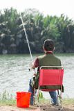 Real fisher. Rear view of a senior fisher sitting and catching the fish royalty free stock photo