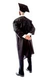 Rear view of a senior male graduate standing with hands behind b Stock Image