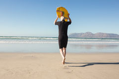 Rear view of senior man carrying surfboard at beach Royalty Free Stock Images