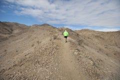 Rear view of senior man jogging on mountain Stock Image
