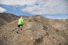 Rear view of senior man jogging on mountain Stock Photos