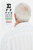 Rear view of a senior man looking at eye chart Royalty Free Stock Photography