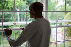 Rear view of senior man looking out through window Stock Images