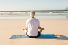 Rear view of senior man meditating at beach Stock Images