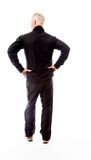 Rear view of a senior man standing with his arms akimbo Stock Image